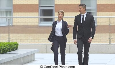 businessman and businesswoman walking on the street of an business center, slow motion