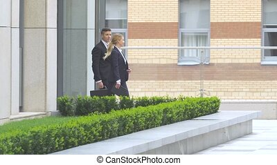 businessman and businesswoman walking on the street of an business center
