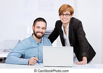 Portrait of happy businessman and businesswoman with laptop at office desk