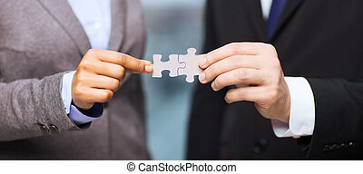 businessman and businesswoman with puzzle pieces