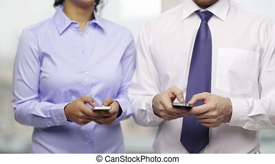businessman and businesswoman with smartphones - business,...