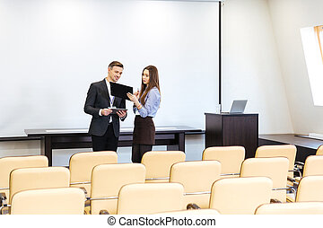 Businessman and businesswoman working in meeting hall
