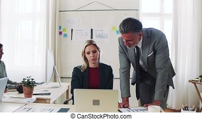 Businessman and businesswoman working together in office, talking.