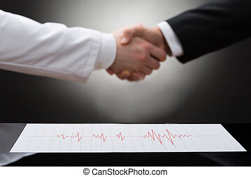 Businessman And Doctor Shaking Hand