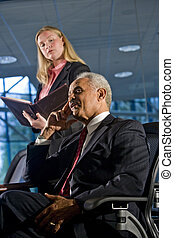Businessman and female assistant in a boardroom meeting