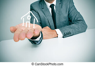 a businessman sitting in a desk showing a drawing of a house in his hand