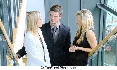 Businessman and two businesswomen talking