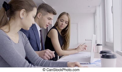 Businessman and two businesswomen working on paper graphs in the office, slow motion.