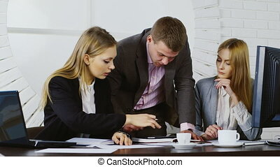 Businessman and two women working with the tablet