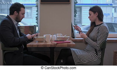 Businessman and woman communicate by smartphones at lunch in cafe