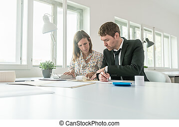 Businessman and woman doing manual accounting