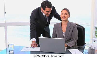 Businessman and woman smiling at the camera