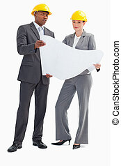 Businessman and woman with hard hats holding paper