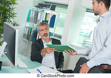 businessman and worker discussing over documents in office
