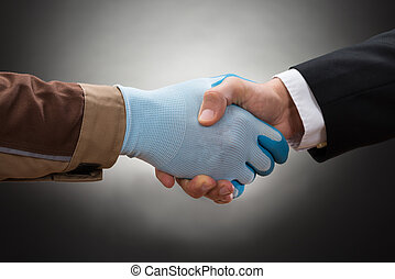 Businessman And Worker Shaking Hand