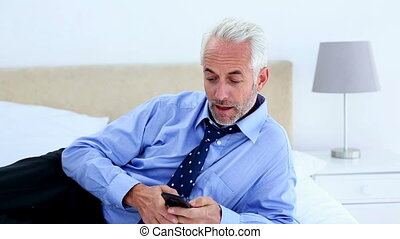 Businessman answering a phone call lying on his bed at home...