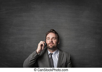 Businessman answering on cord phone