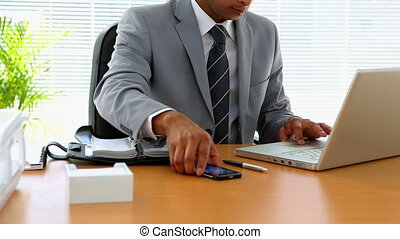 Businessman answering phone at his desk