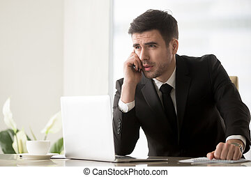 Businessman answering phone call at desk in office