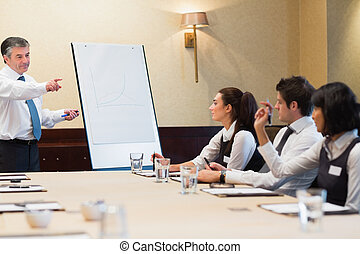 Businessman answering question during presentation in ...