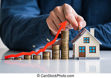 Businessman Arranging Stacked Coins Near House Model