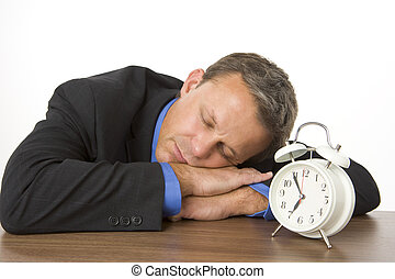 Businessman Asleep On Desk By An Alarm Clock