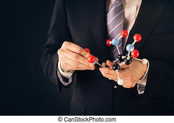 businessman assembling a tnt molecular structure