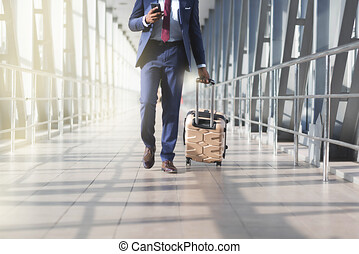 Businessman at airport moving to terminal gate for business trip, front view