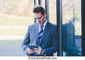 businessman at an office building with a tablet in the hand