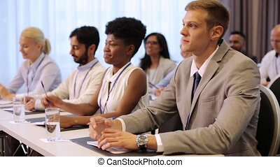 businessman at business conference asking question -...