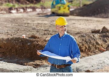 Businessman At Construction Site - Businessman examining...