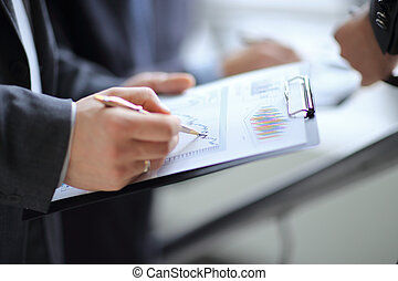 businessman at desk checking a financial report and pointing at