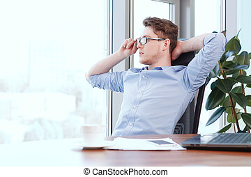 Businessman at desk with hands behind his head
