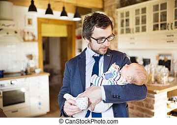 Businessman at home holding baby daughter in the arms.