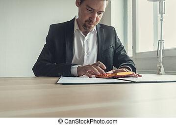Businessman at office desk using calculator