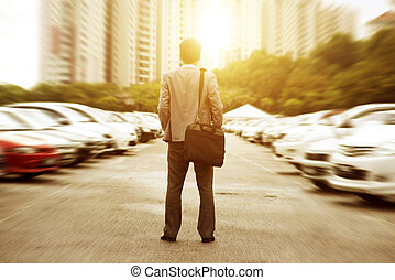 Businessman at open car park.