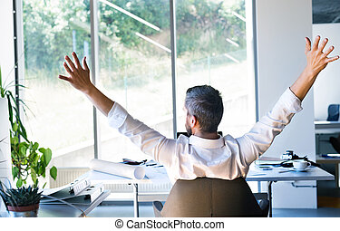 Businessman at the desk in his office stretching arms.