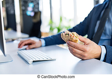 Businessman at the desk with computer eating lunch.