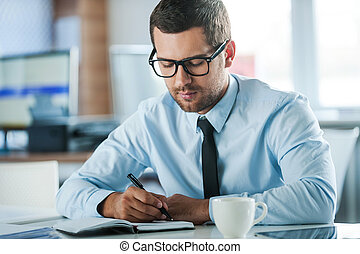 Businessman at work. Confident young businessman in formalwear writing in note pad while sitting at his working place