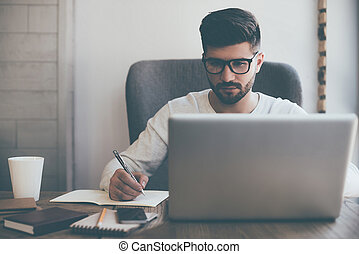 Businessman at work. Confident young man writing something in notebook while sitting at his working place in office