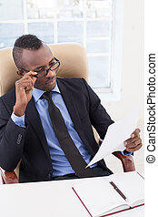 Businessman at work. Top view of confident young African businessman looking at the paper and adjusting his glasses while sitting at his working place