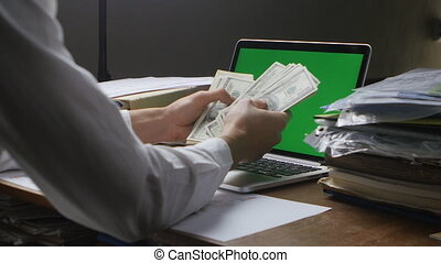 Businessman at workplace counting Many American 100 bills. Concept of salary or making money. Laptop with a green screen on the desk