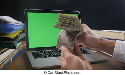 Businessman at workplace counting Many American 100 bills with laptop with a green screen on the desk. Concept of salary or making money.