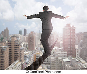 Businessman balancing on a wire with sky clouds cityscape...