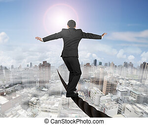 Businessman balancing on a wire with sun mist cityscape