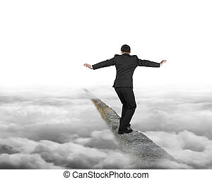 Businessman balancing on concrete ridge with gray cloudy sky