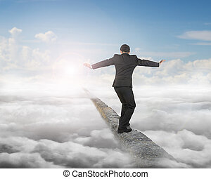 Businessman balancing on concrete ridge with sky sunlight clouds