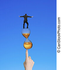 Businessman balancing on hourglass of index finger pointing at