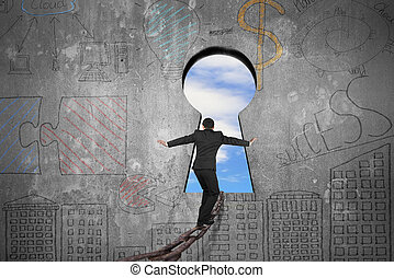 Businessman balancing on iron chain toward keyhole with sky clouds