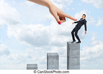 Businessman balancing on vertical concrete column with a giant female hand pointing at him.
